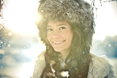 Portrait of a beautiful girl in a fur hat in backl. Cute portrait of a beautiful girl in a fur hat in backlit Royalty Free Stock Photos