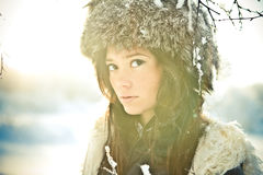 Portrait of a beautiful girl in a fur hat in backl stock image