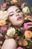 Portrait of a beautiful girl with a gentle pink make-up and lots of flowers in her hair. Beauty face. Royalty Free Stock Photo