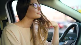 Portrait of a beautiful girl in glasses in the car. Portrait of a beautiful woman in glasses is sitting in the car on the parking near the shopping center stock footage