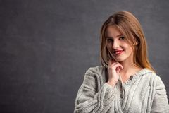 Beautiful Eye-catching Girl. Portrait of beautiful girl in gray sweater, indoor shot in the gray background Royalty Free Stock Photo