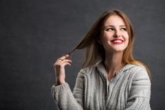 Beautiful Eye-catching Girl. Portrait of beautiful girl in gray sweater playing with her hair, indoor shot in the gray background Stock Photos
