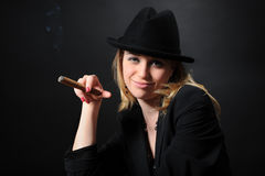 Portrait of a beautiful girl in a hat with a cigar Royalty Free Stock Photography