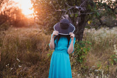 Portrait of a beautiful girl in a hat in a field in sunset light Royalty Free Stock Photo