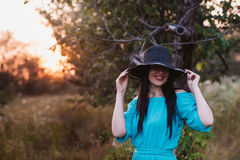 Portrait of a beautiful girl in a hat in a field in sunset light Royalty Free Stock Image