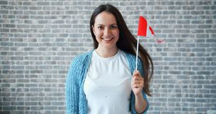 Portrait of beautiful girl holding Canadian flag on brick wall background. Smiling looking at camera alone. Travelling, world countries and people concept stock video footage