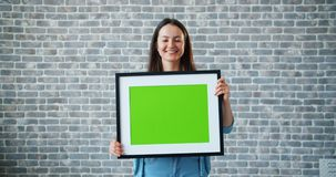 Portrait of beautiful girl holding green chroma key mockup picture and smiling