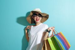 Portrait of beautiful girl holding shopping bags isolated over blue background stock image