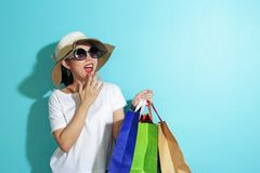 Portrait of beautiful girl holding shopping bags isolated over blue background royalty free stock image