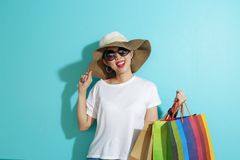 Portrait of beautiful girl holding shopping bags isolated over blue background royalty free stock photography