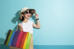 Portrait of beautiful girl holding shopping bags isolated over blue background royalty free stock photo