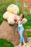 Portrait of a beautiful girl with a huge bear. In the park Stock Photography