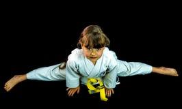 Portrait of beautiful girl in kimono exercising. Full-length silhouette portrait of beautiful martial arts girl in kimono exercising karate kata on black Stock Photo
