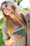 Portrait of beautiful girl listening to music with digital table Royalty Free Stock Photo