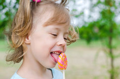 Portrait of a beautiful girl with a lollipop, free space. Happy. Child with a lollipop Royalty Free Stock Images