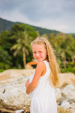 Portrait of a beautiful girl with long hair in a white dress, walking along the seashore Royalty Free Stock Photography