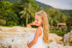 Portrait of a beautiful girl with long hair in a white dress, walking along the seashore Stock Photography