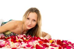 Portrait of a beautiful girl lying in rose petals Royalty Free Stock Photography