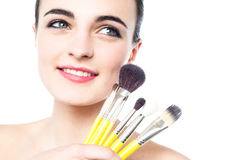 Portrait of a beautiful girl with makeup brushes Royalty Free Stock Image