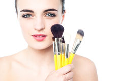 Portrait of a beautiful girl with makeup brushes Stock Images
