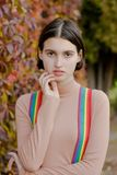 Portrait of a beautiful girl in multi-colored suspenders stock photo