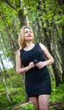 Portrait of a beautiful girl on the nature, in the woods, in a black dress. Stock Photo