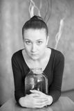 Beautiful girl. Sad young girl with a jar, wide open eyes,  monochrome soft focus portrait Stock Photography