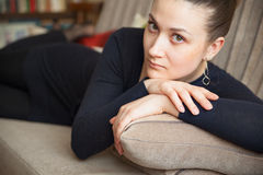 Beautiful women. Serious young European girl on couch at home Royalty Free Stock Photos