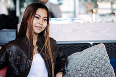 Portrait of beautiful girl with a nice smile in a cafe. Beautiful girl in leather jacket in a cafe Royalty Free Stock Photography