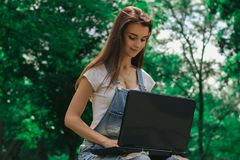 Portrait of a beautiful girl in the Park against the backdrop of trees with a laptop. Portrait of a beautiful girl in the summer in the Park against the backdrop Royalty Free Stock Photography