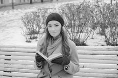 Portrait beautiful girl in the Park with a book sitting on a bench, black and white Royalty Free Stock Photos
