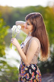 Portrait of beautiful girl in the park holding dandelions Royalty Free Stock Images