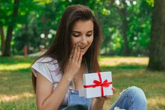 Portrait of a beautiful girl in the park with a surprised gift Royalty Free Stock Photo