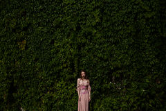 Portrait of beautiful girl in pastel pink dress and corset and flower emboidery. Posing in green climbing vines stock photo