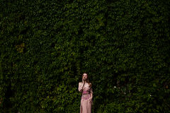 Portrait of beautiful girl in pastel pink dress and corset and flower emboidery. Posing in green climbing vines royalty free stock photography