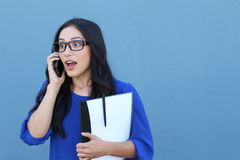 Portrait of a beautiful girl on the phone while getting shocking or surprising news Royalty Free Stock Photography