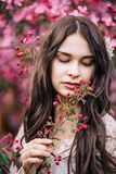 Portrait of beautiful girl in a pink dress, looking down with half open lips, keeps on hand a twig with buds, close-up royalty free stock images