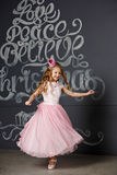 Portrait of a beautiful girl in a pink princess crown on dark ba. Ckground and the snow in the studio Royalty Free Stock Image