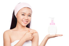 Portrait of beautiful girl pointing a finger. Care cream bottle. isolated on white background Stock Photography