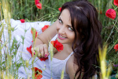 Portrait of the beautiful girl in a poppy field Royalty Free Stock Image