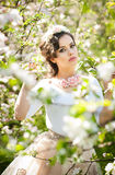 Portrait of beautiful girl posing outdoor with flowers of the cherry trees in blossom during a bright spring day Royalty Free Stock Images