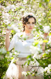 Portrait of beautiful girl posing outdoor with flowers of the cherry trees in blossom during a bright spring day Stock Photography