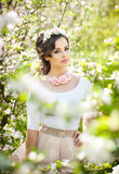 Portrait of beautiful girl posing outdoor with flowers of the cherry trees in blossom during a bright spring day Royalty Free Stock Photography