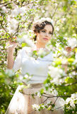 Portrait of beautiful girl posing outdoor with flowers of the cherry trees in blossom during a bright spring day Stock Photos