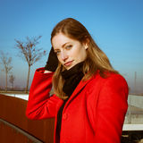 Portrait of a beautiful girl posing with red coat. Portrait of a beautiful girl posing in the street with red coat Royalty Free Stock Photography