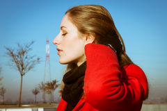 Portrait of a beautiful girl posing with red coat. Portrait of a beautiful girl posing in the street with red coat Stock Photos