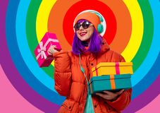 Girl with purple hair with headphones and gifts stock photography