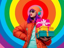 Girl with purple hair with headphones and gifts stock image