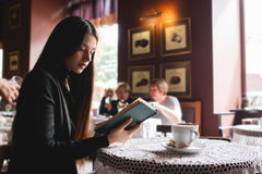 Portrait of a beautiful girl reading book in cafe. drink stock photos