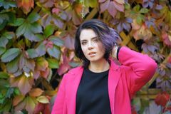 Portrait of a beautiful girl in a red coat. In an autumn park Stock Images
